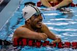 a male Para swimmer laughs in the pool