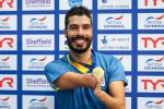 a male Para swimmer smiles while holding up his gold medal