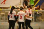 three female goalball players hug in celebration in front of the goal
