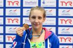 a female Para swimmer holds up a medal and smiles
