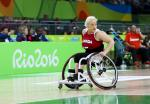 Women in wheelchair dribbles basketball