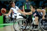 Woman in wheelchair holding a basketball while another tries to defend her