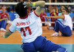 a female sitting volleyball player prepares to serve