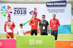Athletes and their guides pose on the podium