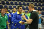 male goalballer player Leomon Moreno receives a trophy and shakes hands with another man