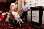 Polish male swimmer Juliusz Trochimczuk in a wheelchair receives an award from two men