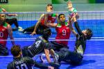 Japanese sitting volleyball player sets the ball while an Iranian athlete prepares to block