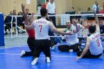 The Iranian men's sitting volleyball team throw their arms up in celebration on the court