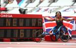 Female wheelchair racer Kare Adenegan holds up a British flag next to the display of her world record time