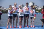 a group of five British Para rowers standing on the podium with their gold medals