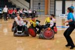 two Colombian wheelchair rugby players tackling a Polish player for the ball