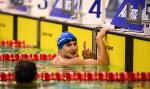 male Para swimmer Francesco Bocciardo races his finger in the pool after winning his race