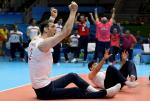 male sitting volleyball player Morteza Mehrzadselakjani raises his arms in celebration on the court