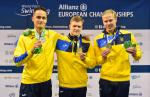 three male Ukrainian swimmers on the podium holding their medals