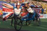 Great Britain's Kare Adenegan nd Hannah Cockroft racing wheelchairs pose with Union Jack flags behind thier backs