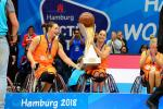 female wheelchair basketballer Carina de Rooij lifts up the trophy