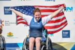 female Para rower Hallie Smith smiling and holding up a USA flag
