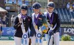 three female Para equestrian riders with Rixt van der Horst in the centre, standing on the podium