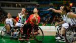 A Chinese female wheelchair basketballer holds off a challenge to the ball
