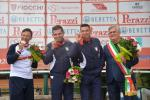 three male Para shooters with Francesco Nespeca in the middle, biting their medals