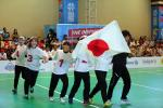 Japanese female goalball players run across the court holding a Japan  flag