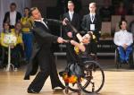 A woman in wheelchair dances with a man standing up