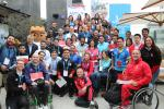 a group of people and the Lima 2019 mascot smile for a photo