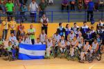 Nicaragua's wheelchair basketball players on a court holding up the Nicaragua flag
