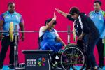 Woman powerlifter on a bench celebrating with another woman
