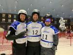 Three men with helmets in an indoor ski resort