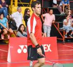 Peruvian male badminton player with prosthetic leg stands holding a racket