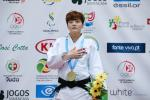 female judoka Soohee Choi holds her hand over her heart on the podium with a gold medal round her neck
