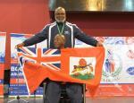 male boccia athlete Steve Wilson on the podium holding up a Bermuda flag