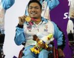 male boccia player Worawut Saengampa smiles and holds up his gold medal