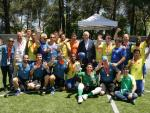 a group of male blind footballers wearing Brazil shirts and holding their hands up in celebration