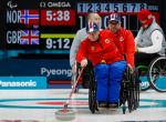 male wheelchair curler Rune Lorentsen pushes a curling stone out onto the ice