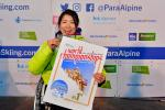 female Para alpine skier Momoka Muraoka holds up her gold medal and a banner