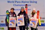 three female skiers including Marie Bochet standing on the podium holding prints