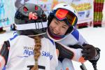 female Para alpine skier Momoka Muraoka hugs another female skier and smiles