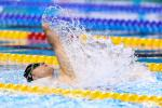 male Para swimmer Cameron Leslie lifts his arm up out of the water during a backstroke race