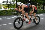 male Para triathlete Dave Ellis cycling on a tandem bike behind his guide