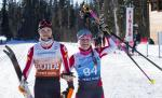 female vision impaired skier Carina Edlinger and her male guide raise their arms in celebration