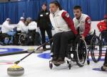 a female wheelchair curler from Latvia plays a stone while another curler holds her wheelchair to steady it