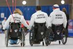 three wheelchair curlers with their backs to the camera with Norway on their jackets