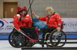 Two men and woman in wheelchairs celebrating on a curling rink