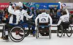 Four wheelchair curlers celebrating and waving to the crowd