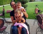 female Para rower Moran Samuel in a wheelchair with her two children on her lap