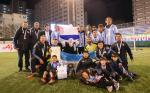 A group of male blind footballers stand with a blindfolded mascot holding a trophy and the Argentinian flag