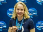 female Para swimmer Julia Gaffney smiles and holds up a gold medal
