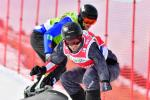 male Para snowboarder Patrick Mayrhofer rides in front of another snowboarder